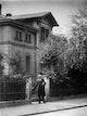 Abbe mit Strohhut am Gartentor seines Hauses um 1900.